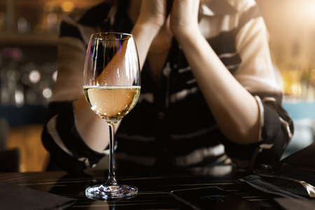 Closeup view of white wine glass on table against young adult woman sitting on ddating at cafe or restaurant at warm sunset time. Alone single female person drinking champagne at bar