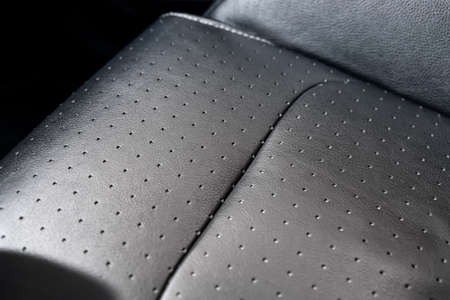 Close-up detail view of modern black perforated dotted ventilated luxury car seat. Part of dark vehicle interior. Auto detailing and leather polish skin cleaning wash and care concept