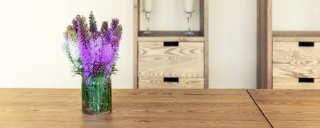 Beautiful fresh natural lilac purple liatris flower bouquete in glass jar on rural wooden table against wall with cabinet shelf. Rustic countryside cottage interior wildflowers bunch. wide banner