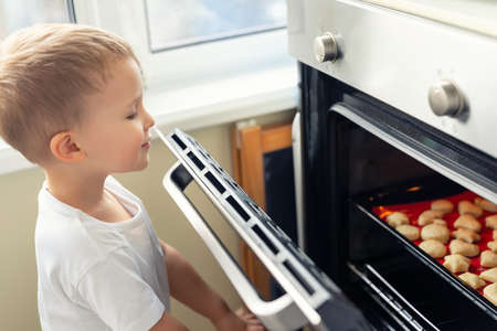 Cute adroable little caucasian blond 3-4 years boy enjoy have fun looking in open oven door checking baking sweet holiday homemade cookies. Impatient funny curious happy kid at kitchen at home Stockfoto