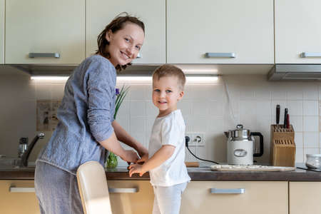 Portrait young adult mother learn cooking sweet tasty cookies cute little toodler boy kid at home kitchen. Mom with small son baking sweet pastry homemade dessert. Parent child together activity