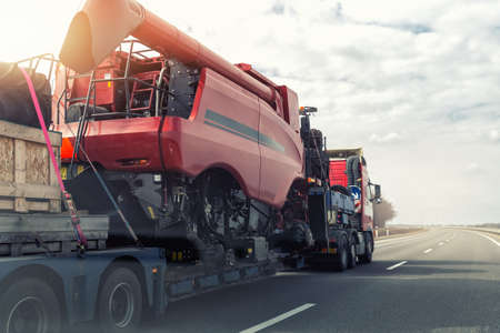 Heavy industrial truck with semi trailer platform transport disassembled combine harvester machine on common highway road on sunset or sunrise day. Agricultural equipment transportation service