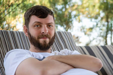 Close-up portrait of young adult cuacasian bearded man enjoy chilling on sofa at yard outdoors on sunny warm summer day. Happy smiling male person rest in park outside