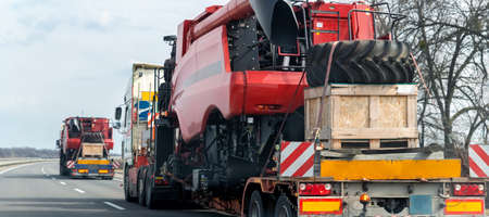 Many heavy industrial truck with semi trailer platform transport disassembled combine harvester machine on public highway road on sunset or sunrise day. Agricultural equipment transportation service 版權商用圖片