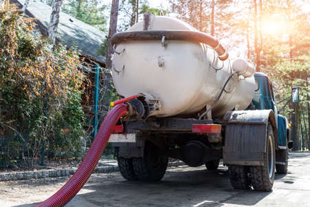 Close-up pipe hose of sewage truck car engine emptying home sewerage tank. Septic cleaning vacuum service and maintenance suburban countryside home. Suction vehicle cleaner machine pumping drainage 版權商用圖片