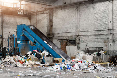 Shreding wastepaper mill conveyor belt for recycling paper wrap, garbage and cardboard against bales of used carton boxes collected for recycle and reuse at industrial plant or factory.Sustainable