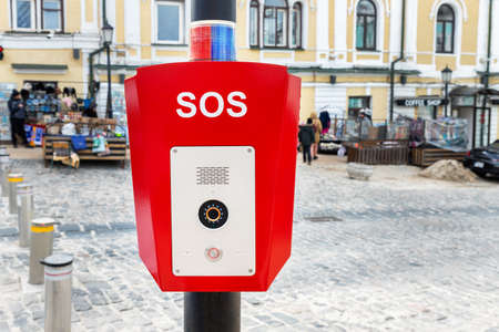 Red emergency police SOS call button alarm box with light bar, cctv camera and speaker device for urgent comunication on city street. Modern smart communication technology public space. Civil safety