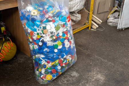 Many multicolored plastic caps from water pet bottles collected in bag for recyclyng and reuse. Environmental protection from pollution