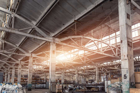 Old abandoned decay industry factory or plant building interior with concrete and steel metal construction frame beams. Sunlight warm sun through rooftop window. Dark grungy industrial background