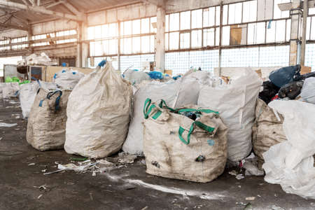 Heap of many dirty big bag containers with used water pet bottles collected for recyclyng and reuse at abandoned recycling factory warehouse. Environmental protection from pollution