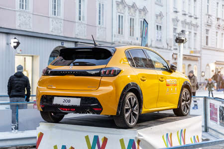 Wels, Austria - January 11th,2020: Newest Peugeot 208 gt-line 2020 model stand on basement among public skating rink in center old european city Wels. Vehicle advertisment and presentation in Europe