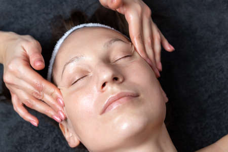 Close-up beautician doctor hand making anti-age wrinkles facial massage procedure applying lotion to attractive adult female client at beauty clinic. Cosmetologist do skincare. Healthcare therapy 版權商用圖片