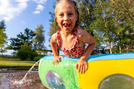 Cute adorable playful caucasian blond kid girl enjoy having fun swimming and splashing in small inflatable pool at house garden yard on hot summer day. Children outdoor healthy acivities