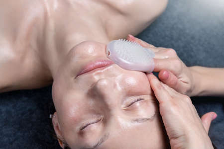 Close-up beautician doctor hand making anti-age procedure face massage with silicone glove applying lotion to attractive female client at beauty clinic. Cosmetologist do skincare. Healthcare therapy 版權商用圖片