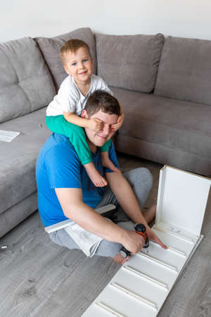Cute adorable caucasian toddler boy kid sit on fathers neck and help assembling furniture shelf with power screwdriver tool. Young adult dad with funny little child enjoy playing at home indoors