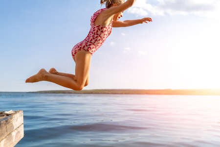 Little cute kid girl in swimsuit have fun enjoy pretend flying jumping from pier dock in clean blue water sea river or ocean on hot summer evening sunset. Carefree children lifestyle vacation concept