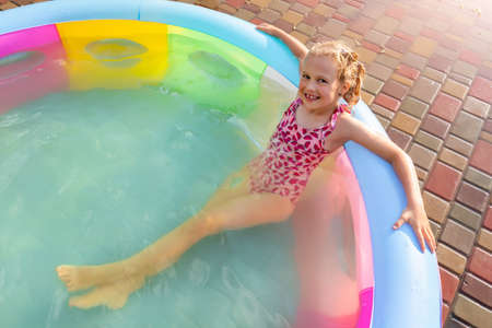 Cute adorable playful caucasian blond kid girl enjoy having fun swimming and relaxing in small inflatable pool at house garden yard on hot summer day. Children outdoor healthy acivities