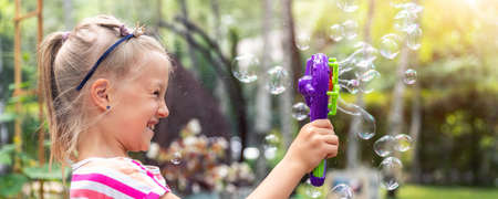 Portrait of cute little bond kid girl enjoy having fun play blowing soap bubbles at home yard garden outdoors on bright warm summer day against lawn and trees. Child healthy outside nature activities