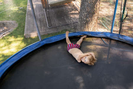 Top above view of cute little caucasian funny blond toddler boy lying inside big black trampoline at home backyard playground area outdoors on warm summer day. Children street sport activity