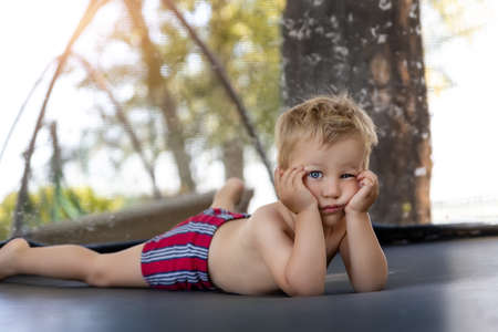Portrait of cute bored little caucasian funny sad blond toddler boy lying inside big black trampoline at home backyard playground area outdoors warm summer sunny day. Children street sport activity