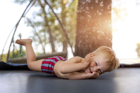 Top above view of cute little caucasian funny blond toddler boy lying inside big black trampoline at home backyard playground area outdoors on warm summer sunny day. Children street sport activity