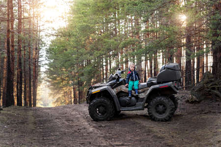 Cute adorable little blond caucasian toddler boy siiting on ATV quad motorcycle along rural country sand road on ranch or farm at coniferous forest sunrise morning. Small kid discover nature outdoors