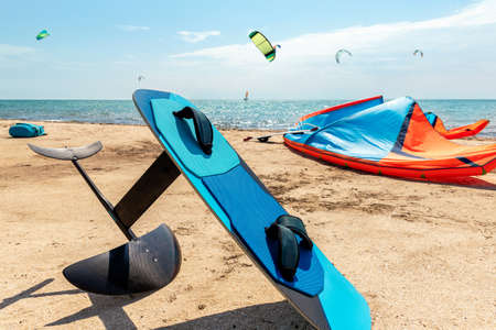 Close-up hydrofoil surf board and kite equipment on sand beach shore watersport spot on bright sunny day against sea ocean coast with many kiter riding surf school camp. Active travel sport concept