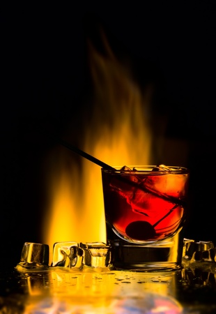 Cocktail with fire and an ice Stock Photo
