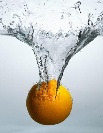 The orange falls in water