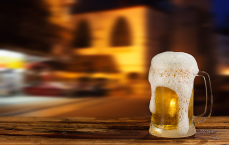 cold mug of beer with foam on the background of the street