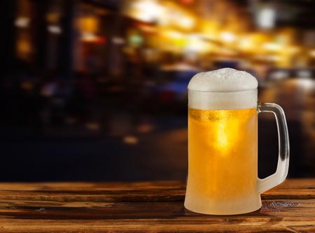 kaltes Glas Krug Bier mit Schaum auf dem Hintergrund der Straße Editorial