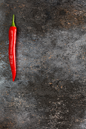 Red hot chili pepper on grunge background.Top view, flat lay design.