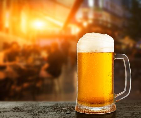 Tazza con birra sullo sfondo di un bar esterno. Archivio Fotografico
