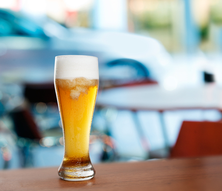 cold glass with beer on the background of a outside bar. Stock Photo