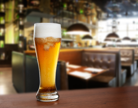 cold glass with beer on the background of bar.