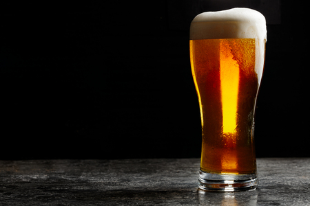 Glass of cold craft light beer on dark background. Stock Photo