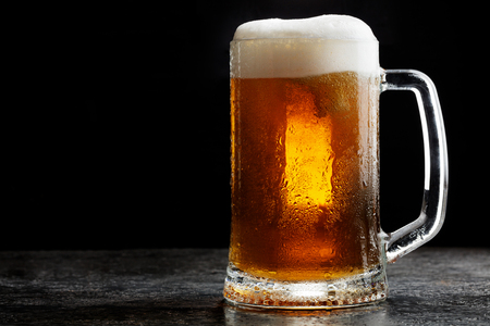 Mug of cold craft light beer on dark background.