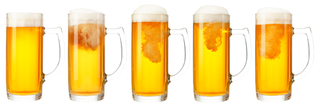 Set of mugs of cold light beer with foam isolated on white background