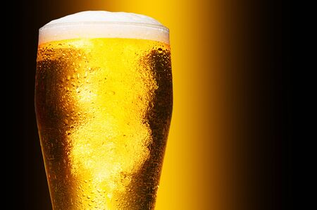Glass of cold craft light beer on dark background. Standard-Bild