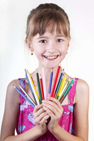 Young girl with pencils on white background photo