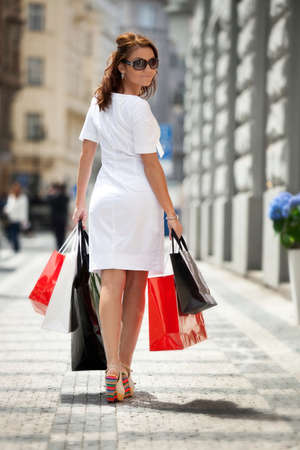 human photography: Muchacha hermosa joven con bolsas de compras caminando por la calle en Praga.