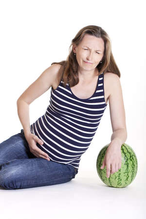Pregnant woman with big green watermelon, studio shot on white background photo
