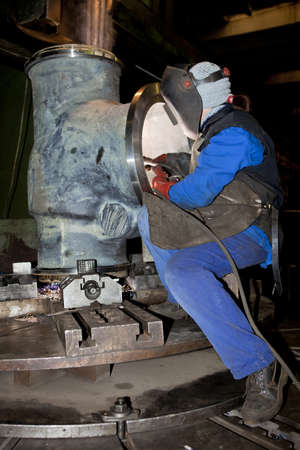 Welder worker is welding a big valve  body photo