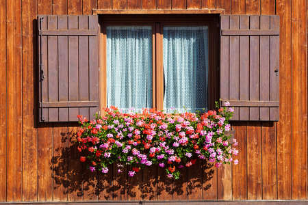 Wooden window with shutters open on and flowers in hanging flower tray photo