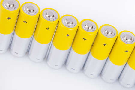 alkaline: Raw of yellow AA alkaline batteries isolated on white background Stock Photo