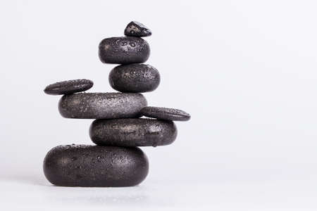 Wet smooth polished hot massage black stones covered with water drops