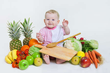 Cute baby  sitting with fruits and vegetables and hold an apple isolated on white background. Concept: healthy vitamin vegetable food diet make baby strong and happy