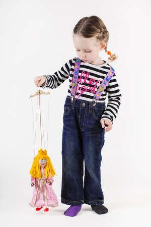 marioneta de madera: Niña linda que juega con títeres, aislado en blanco Foto de archivo
