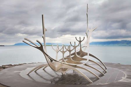 voyager: REYKJAVIK, ICELAND - Jun 19th, 2014 - Sculpture of Sun Voyager monument, landmark of Reykjavik city, designed by Jon Gunnar Arnason, at the clear spring evening  with sea and mountains in background in Reykjavik, Iceland