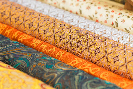 canva: Rolls of fabric and textiles in a factory shop. Multi different colors and patterns on the market Stock Photo